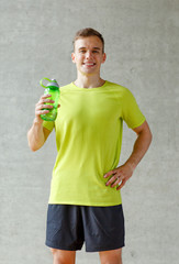 smiling man with bottle of water in gym