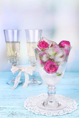 Ice cubes with rose flowers in glass bowl and two glasses with