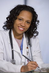 African American female doctor writing in chart
