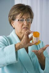 Senior Hispanic woman holding empty medication bottle