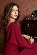 The elegant sensual young woman in a claret dress