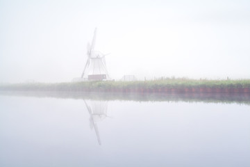 windmill reflected in river and dense fog