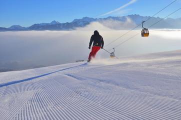 Skifahrer bei Abfahrt mit Gondel