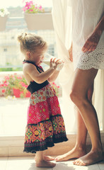 beautiful mother and daughter standing near the window