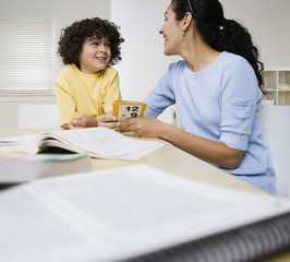 Hispanic mother helping son with homework