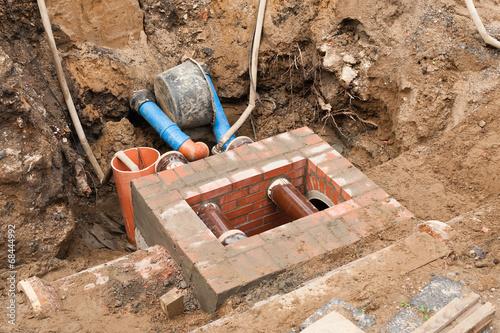 Mauerarbeiten an einem kleinen Abwasserschacht - 68444992