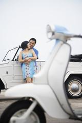 Asian couple hugging against car