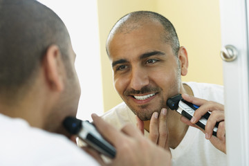 Middle Eastern man shaving with electric razor