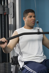 Hispanic man using weight machine