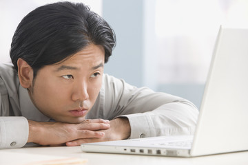 Asian businessman looking at laptop