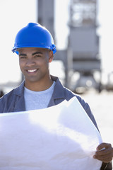 African American male construction worker holding blueprints