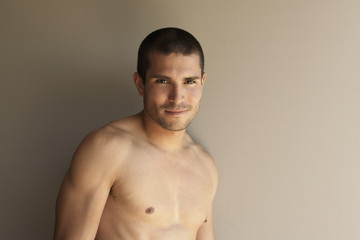 Bare-chested Native American man leaning on wall