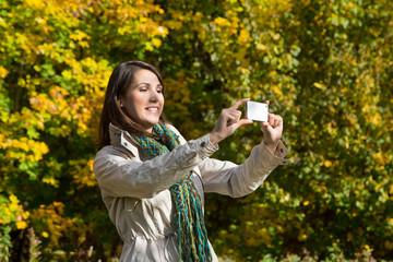 Glückliche junge Frau im  Herbst mit Smartphone