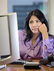 Hispanic businesswoman looking at computer