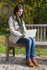 Herbst: junge Frau sitzt im Garten und schreibt eine Nachricht