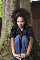 African woman sitting against tree