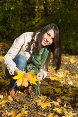 Glückliche lachende junge Frau im Herbst -
