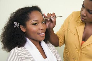 African woman having makeup applied