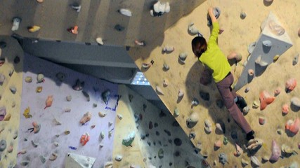 Child exercising in bouldering gym