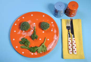 Health food concept with happy vegetable face on plate