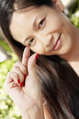 Asian woman holding out thumb and index finger
