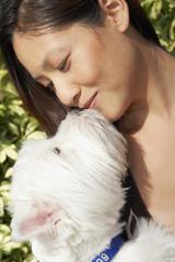 Asian woman kissing dog