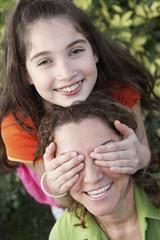 Hispanic girl covering mother's eyes