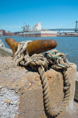 Rusted ship cleat and rope in dock