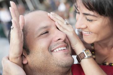 Hispanic woman covering husband's eyes