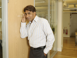 Indian businessman listening through wall with glass