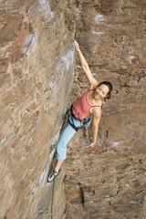 Asian woman rock climbing