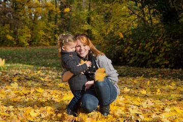 Mutter und Kind im Herbst spielen mit Blättern