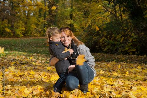 canvas print picture Mutter und Kind im Herbst spielen mit Blättern