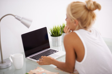 Blonde woman using her laptop in her worksapce. View from behind