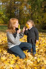 Glückliche Familie: junge Mutter mit ihrer Tochter im Herbst