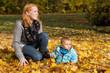Glückliche junge Mutter mit Baby im Herbst