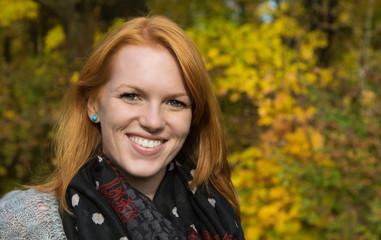 Portrait: glückliche lachende junge rothaarige Frau im Herbst