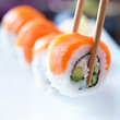 picking up a piece of sushi with chopsticks - 68450395
