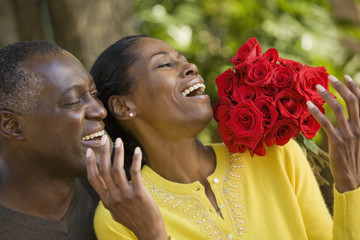 African man surprising wife with flowers
