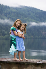 Asian sisters hugging on dock