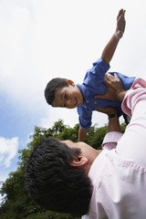 Hispanic father holding son in air
