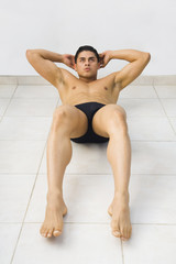 Bare-chested Hispanic man doing sit-ups