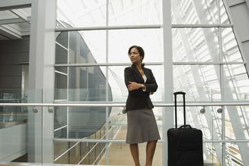 Hispanic businesswoman standing next to suitcase