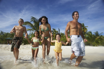 Hispanic family running into water