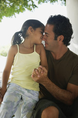 Hispanic father and daughter hugging