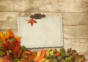 Vintage wooden background with card&autumn decorations