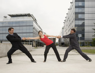 Multi-ethnic businessmen having tug of war with woman