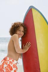 Mixed Race boy holding surfboard