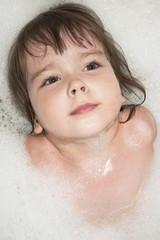 Ребенок в ванной купается в пене для ванн