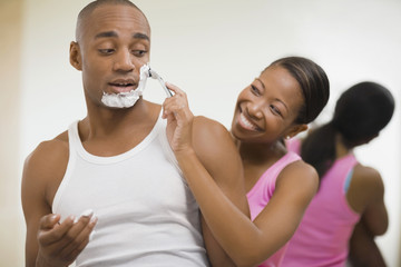 African woman helping husband shave